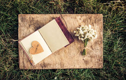 An open book with empty pages, a bouquet of white flowers and a wooden heart. Romantic concept. Copy space Stock Images