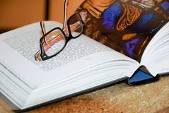 Open book with eyeglasses Stock Photography