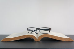 Open book and eyeglasses on desk Royalty Free Stock Images