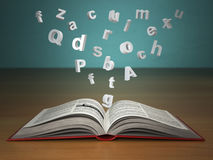 Open book with falling letters on green vintage background. Stock Photos