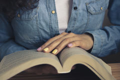Open book in female hands. With bright manicure closeup. The girl in the denim shirt and white shirt holding an open book. Vintage photo Stock Images
