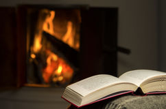 Open book by fireplace. Royalty Free Stock Photos