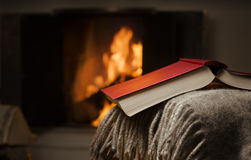 Open book by fireplace. Stock Photos