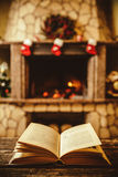 Open book by the Fireplace with Christmas ornaments. Open storyb. Ook lying on a wooden bench by the fireside. Cozy relaxed magical atmosphere in a chalet house royalty free stock photos