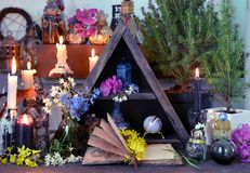 Open book with flowers, candles and magic bottles on witch table. Wicca, esoteric, divination and occult concept with vintage magic objects for mystic rituals royalty free stock photo