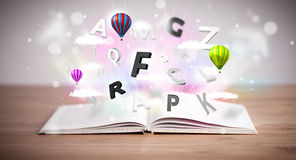 Open book with flying 3d letters on concrete background Royalty Free Stock Photos