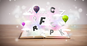 Open book with flying 3d letters on concrete background Royalty Free Stock Images