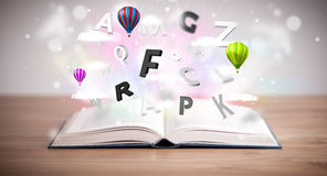 Open book with flying 3d letters on concrete background Stock Photo