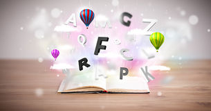 Open book with flying 3d letters on concrete background Stock Images