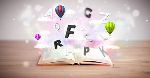 Open book with flying 3d letters on concrete background Stock Photos
