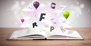 Open book with flying 3d letters on concrete background Royalty Free Stock Photo