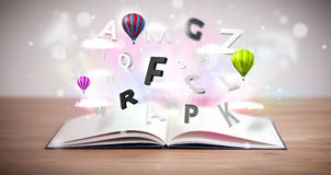 Open book with flying 3d letters on concrete background Stock Image