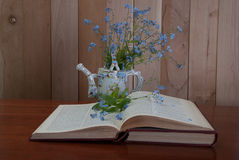 Open book with forget me not flowers. On wooden background Stock Image