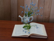 Open book with forget me not flowers. On wooden background Royalty Free Stock Photo