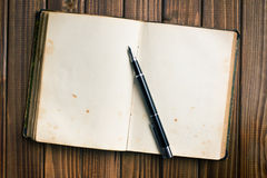 Open book with fountain pen. Top view of old open book with fountain pen on wooden table stock photography