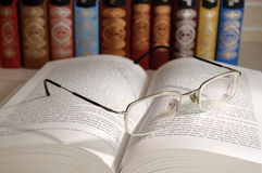 Open book with glasses Stock Photos