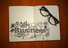 Open book with glasses and black business doodles on table Royalty Free Stock Photos