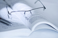 Open book with glasses Royalty Free Stock Images