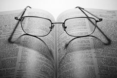 Open book with glasses in dark Royalty Free Stock Image