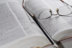 Open book with glasses and pen. Closeup of open book, reading glasses and pencil Royalty Free Stock Photos