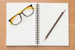 Open book ,glasses and pencil on wood background. Royalty Free Stock Images