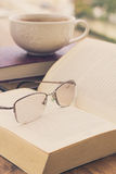 Open book and glasses on a wooden table Stock Image