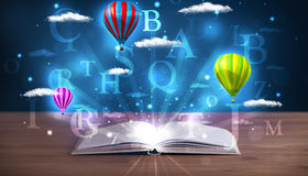 Open book with glowing fantasy abstract clouds and balloons Royalty Free Stock Image
