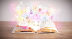Open book with glowing letters on concrete background Stock Photos