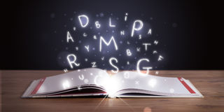 Open book with glowing letters flying Stock Images