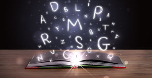 Open book with glowing letters flying out Stock Photos