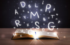 Open book with glowing letters flying out Royalty Free Stock Image