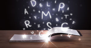 Open book with glowing letters flying out Royalty Free Stock Photography