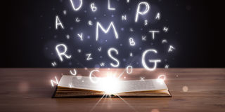 Open book with glowing letters flying out Royalty Free Stock Images