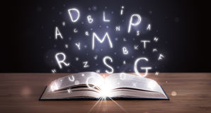 Open book with glowing letters flying out Royalty Free Stock Photos