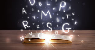 Open book with glowing letters flying out Stock Photography