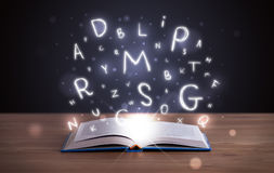 Open book with glowing letters flying out Royalty Free Stock Photo
