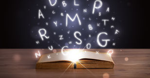 Open book with glowing letters flying out Stock Images
