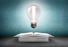 Open book and glowing light bulb with exclamation sign over it. Knowledge, education concept Stock Images