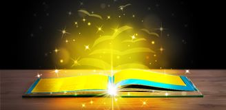 Open book with golden glow flying paper pages. On wooden deck Royalty Free Stock Images