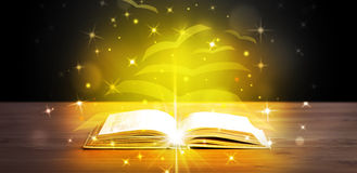 Open book with golden glow flying paper pages Royalty Free Stock Image