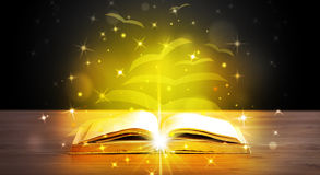 Open book with golden glow flying paper pages. On wooden deck Stock Images