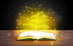 Open book with golden glow flying paper pages. On wooden deck Royalty Free Stock Photos