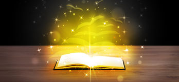 Open book with golden glow flying Stock Photo