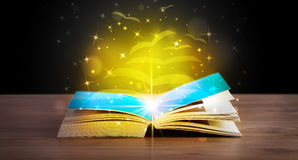 Open book with golden glow flying paper pages Royalty Free Stock Photography