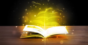 Open book with golden glow flying paper pages Stock Image