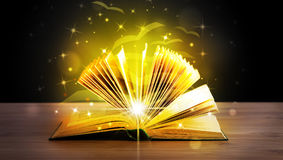 Open book with golden glow flying paper pages. On wooden deck Royalty Free Stock Image