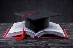 Open book with graduation cap. On wooden table stock images