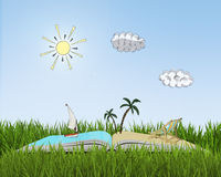 Open book on grass with sketch of beach. Royalty Free Stock Photo