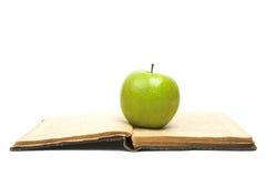 Open Book and green apple Stock Photos