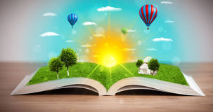 Open book with green nature world coming out of its pages Stock Images